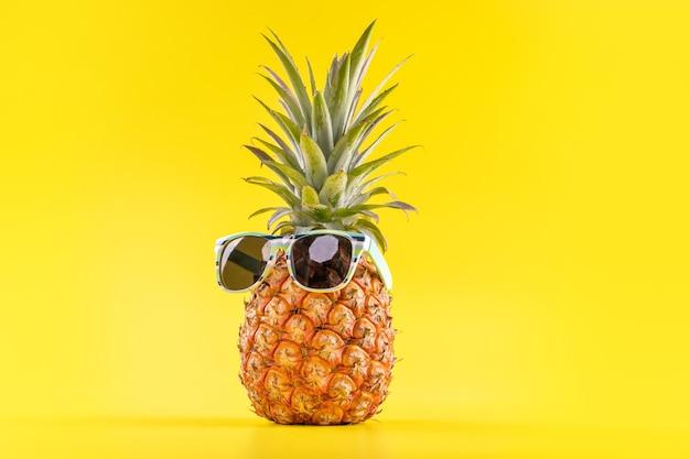 黄色の背景に分離されたサングラス、夏休みのビーチのアイデアデザインパターン、コピースペース、クローズアップ、テキストの空白で創造的なパイナップル Premium写真