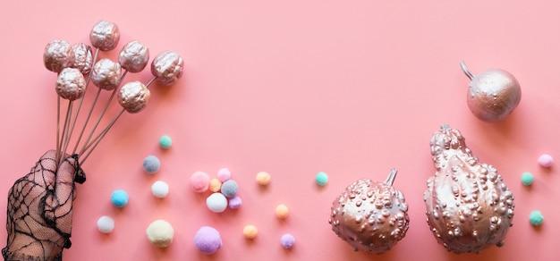創造的なピンクの紙フラットレイアウト、バナー構成。きらびやかな金属製の装飾的なカボチャ、パステルカラーの柔らかいボール、装飾的な果物を保持している黒いメッシュグローブの手でフラットレイアウト Premium写真