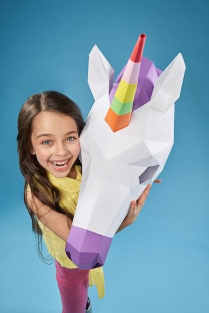 Creative portrait of child with white 3d unicorn head. Free Photo