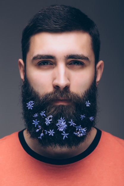 Творческий портрет молодого красивого человека с бородой, украшенный цветами. Бесплатные Фотографии