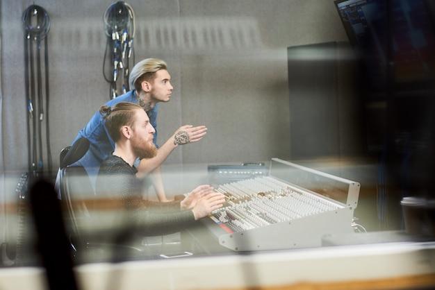 Креативные продюсеры делают музыку в студии Premium Фотографии