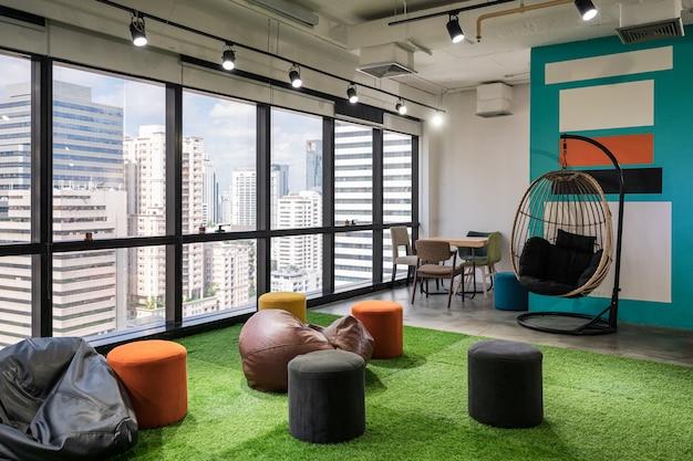 モダンなオフィスの人工芝のクッションと椅子のあるクリエイティブルームコワーキングスペース Premium写真