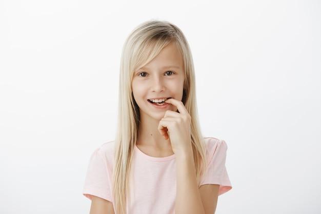 創造的な賢い子供は素晴らしいアイデアを作り上げました。公正な髪の夢のようなかわいい女の子の肖像画、嬉しそうに笑って指を噛む、計画を持っている、または興味をそそる何かをしたい、灰色の壁の上に立って 無料写真