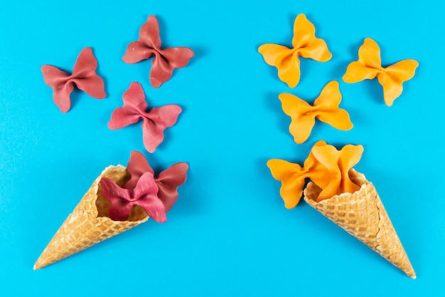 Creative summer layout made of ice cream cone, waffle cones and colored pasta semolina Premium Photo