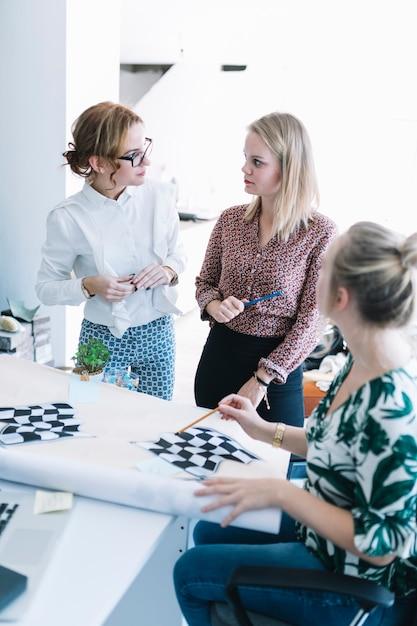 Creative team of businesswomen preparing checkered flag in office Free Photo