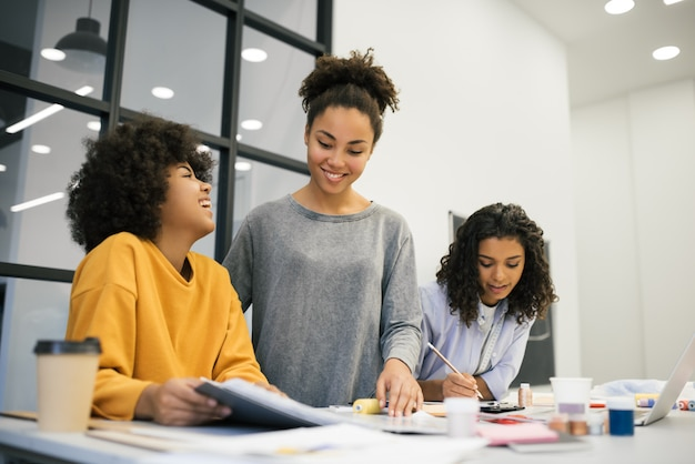 Creative Team Of Smiling Curly African American Women Planning New Startup Project In Workplace Brainstorming University Students Learning Fashion Design At Atelier Young Hipsters Working Together Premium Photo