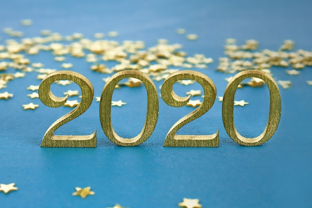 Creative text happy new year 2020 written in gold wooden letters. Premium Photo
