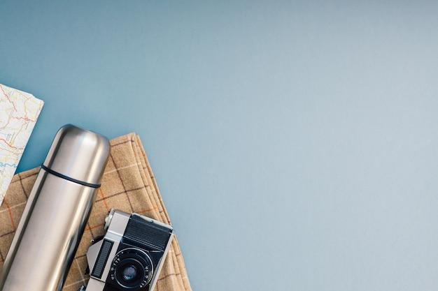 クリエイティブトップビューフラットレイ屋外旅行構成。魔法瓶マップレトロカメラカトラリーブランケットグレーブルー背景コピースペース。 Premium写真