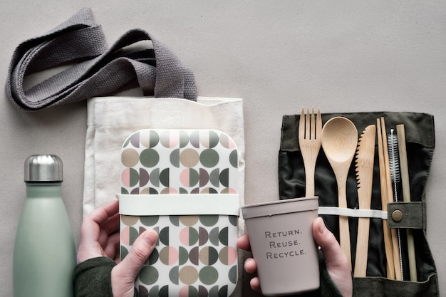 Creative top view, zero waste packed lunch concept, takeaway lunch box set with bamboo cutlery, reusable box, cotton bag and hand with coffee-to-go cup above on craft paper. sustainable lifestyle. Premium Photo
