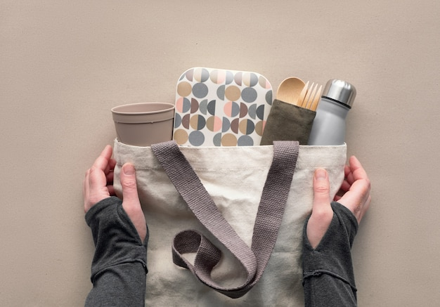Creative top view, zero waste packed lunch kit in canvas bag. hands holding bag with takeaway lunch box, bundle with bamboo cutlery, reusable box and coffee-to-go cup. flat layout on craft paper. Premium Photo