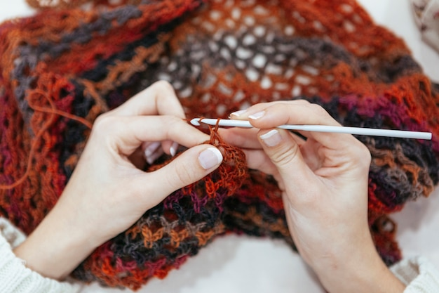 Creative woman knitting a scarf with earth tones of color Premium Photo