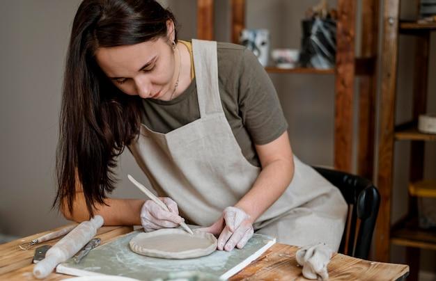 Donna creativa che fa una pentola di creta nel suo laboratorio Foto Gratuite