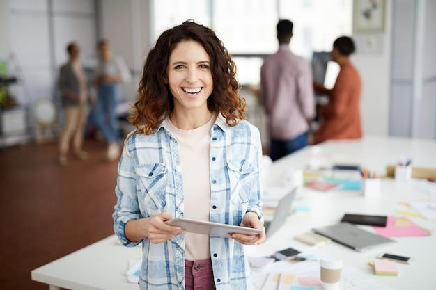 Творческая женщина улыбается в офисе Premium Фотографии