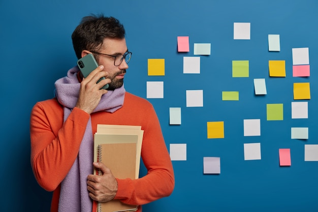 Creative worker with beard calls someone via cellphone, wears eyeglasses, sweater with scarf, looks aside on colorful notes stuck on blue wall Free Photo