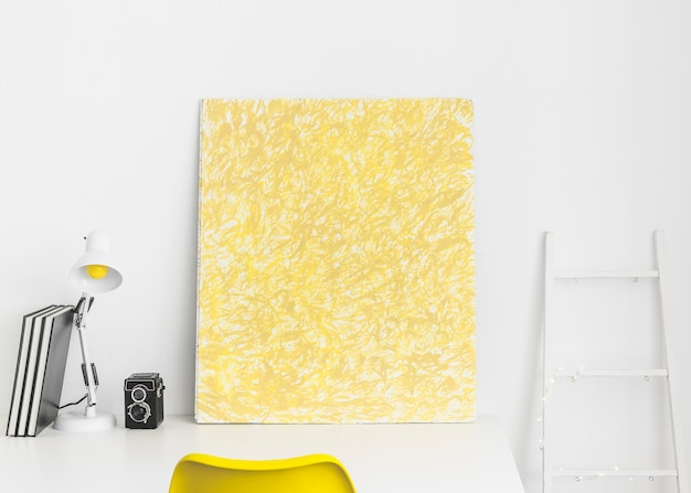 Creative workplace with yellow picture and white ladder Free Photo