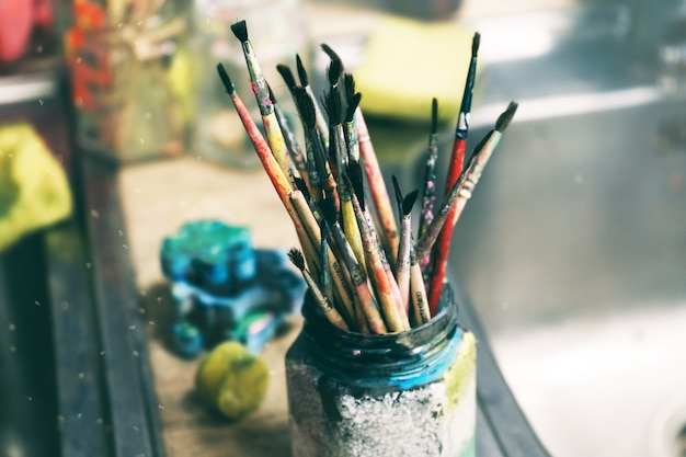 Creative workshop of the artist. paint brushes in a jar. many brushes for painting in one place Premium Photo