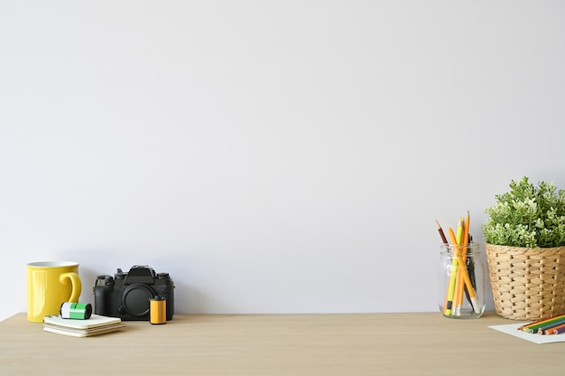 Creative workspace camera and office supplies on wood desk with copy space. Premium Photo