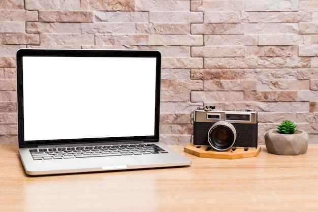 Creative workspace with laptop and retro camera Free Photo