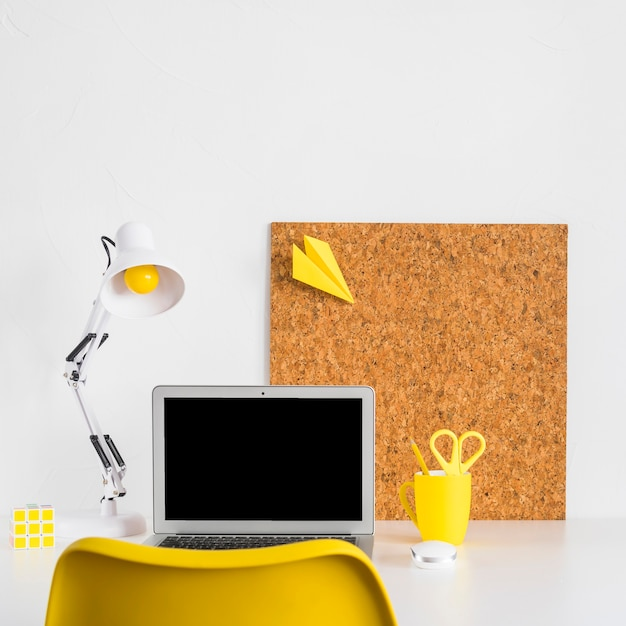 Creative workspace with yellow chair and reading lamp Free Photo