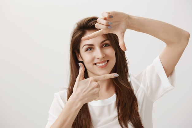 Creative young woman making capture gesture, picturing scene and smiling pleased Free Photo