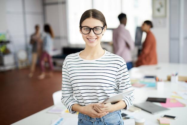 Творческая молодая женщина позирует в офисе Premium Фотографии