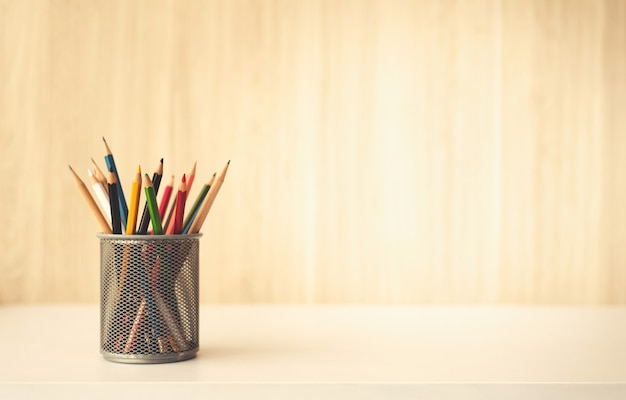 Creativity of colorful pencils in pencil case on wooden table desk background Premium Photo