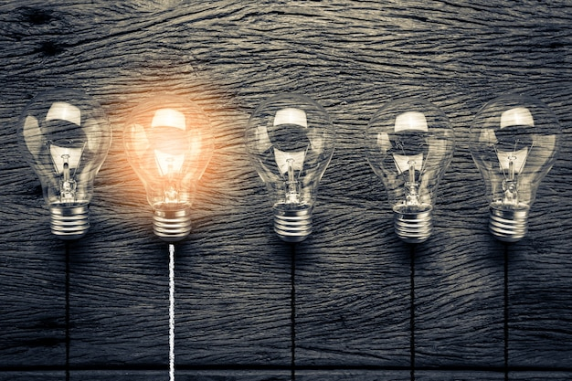 Creativity ideas with light bulb on wooden texture background Premium Photo