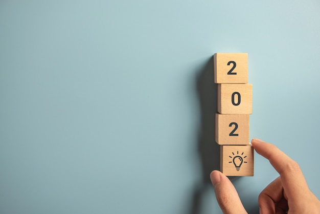 Creativity inspiration concepts, woman hand arranging wood block with new year 2020 and lightbulb icon, planning ideas. Premium Photo