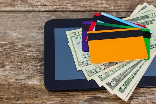 Credit card, dollars, computer tablet on wood Premium Photo