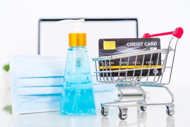 手指消毒剤とサージカルマスクのオンラインショッピングを備えたノートパソコンの画面のクレジットカード前面、covid-19の流行に対する在宅勤務の検疫 Premium写真