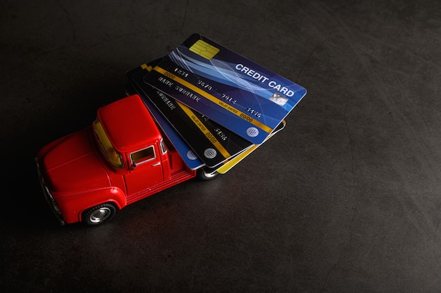 The credit card on the red pickup model on the black floor Free Photo