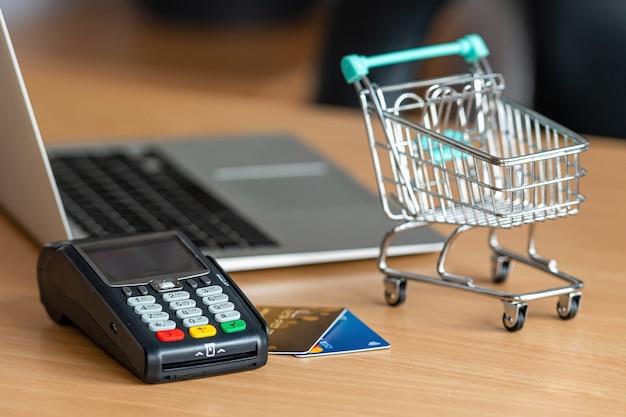 Терминал для кредитных карт на столе в магазине с кредитной картой, ноутбуком и мини-тележкой для покупок Premium Фотографии