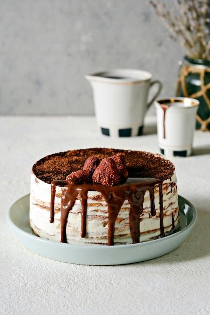 Блинный торт из тонкого блинчика со сливочным кремом, какао, шоколадом, сублимированной клубникой. Premium Фотографии
