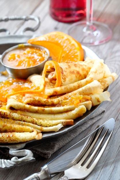 Crepes suzette on vintage metal plate on wooden table served with orange sauce Premium Photo