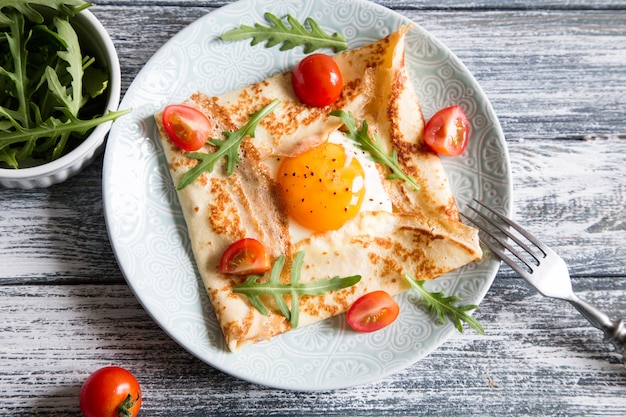 Crepes with eggs, cheese, arugula leaves and tomatoes. galette complete. Premium Photo
