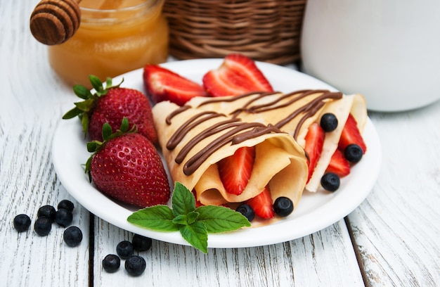 Crepes with strawberries and chocolate sauce Premium Photo