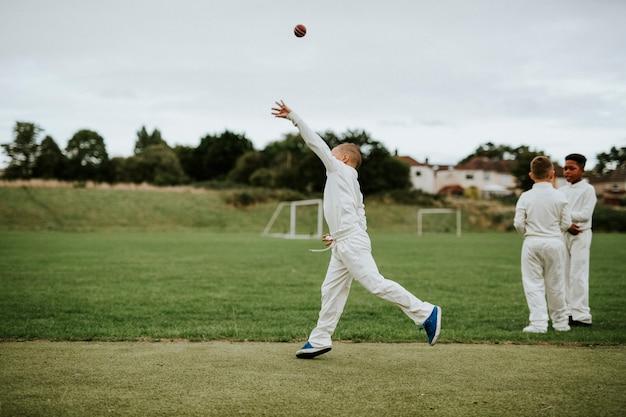 Cricket player catching a ball Premium Photo