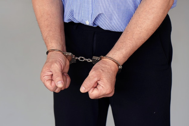 Criminal caucasian hands locked in handcuffs. closeup view. Premium Photo