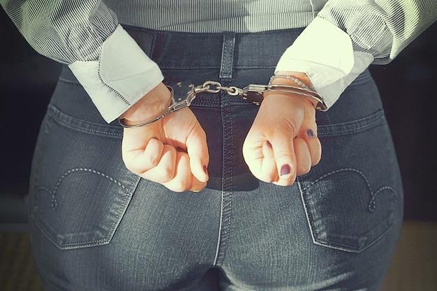 Criminal hands locked in handcuffs. close-up view Premium Photo