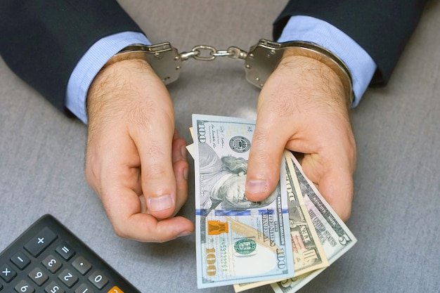 Criminal hands locked in handcuffs. close-up view Premium Photo