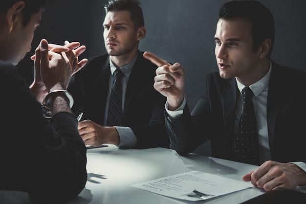 Criminal man being interviewed in interrogation room Premium Photo