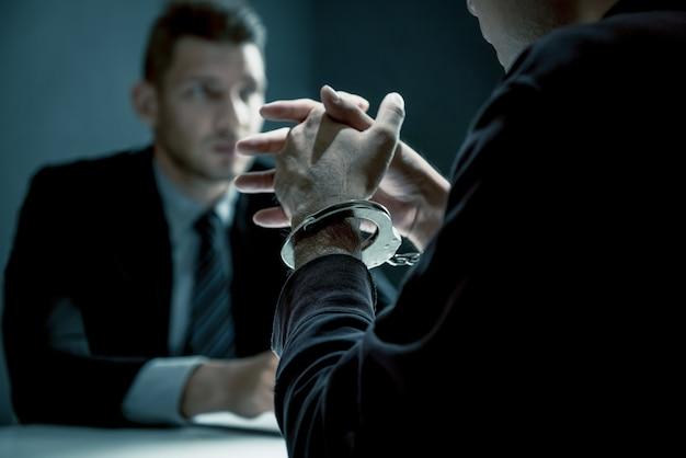 Criminal man with handcuffs being interviewed in interrogation room Premium Photo