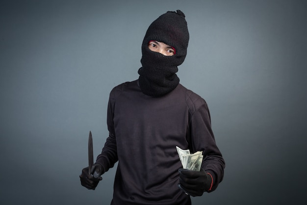 Criminals wear black mask and hold dark on gray Free Photo