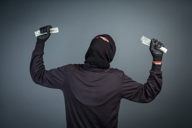 Criminals wear black masks to hold dollar cards on gray Free Photo