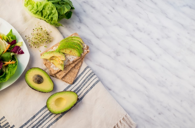 Crisp bread with avocado on table Free Photo