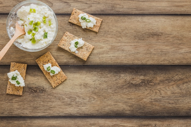 Crisp bread with fresh cream cheese on wooden background Free Photo