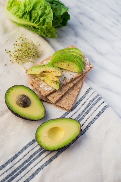 Crisp bread with sliced avocado on table Free Photo