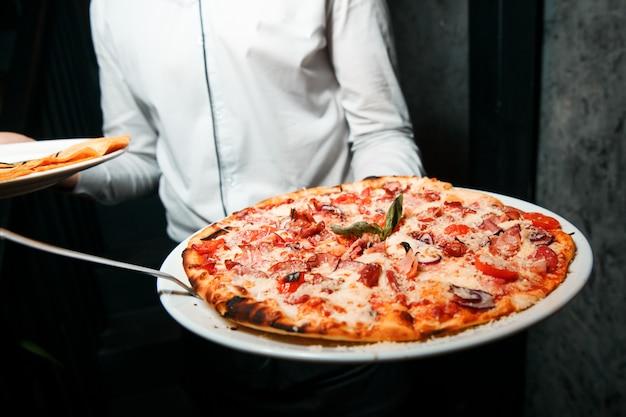 Горячая пицца с плавленым сыром, помидорами и ветчиной. подается на белой круглой тарелке. crisp. Premium Фотографии