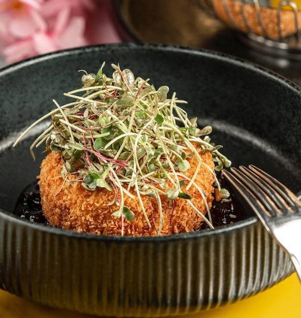 Crispy chicken nugget garnished with fresh herbs Free Photo