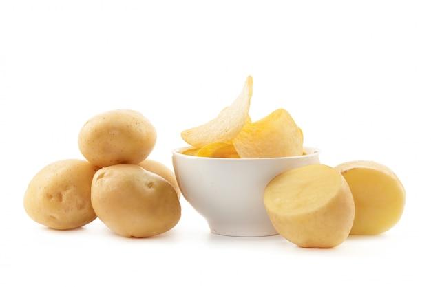 Хрустящие чипсы и сырой картофель на белом фоне Premium Фотографии